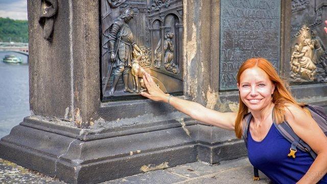 Рыжеволосая туристка трёт на счастье медную собачку