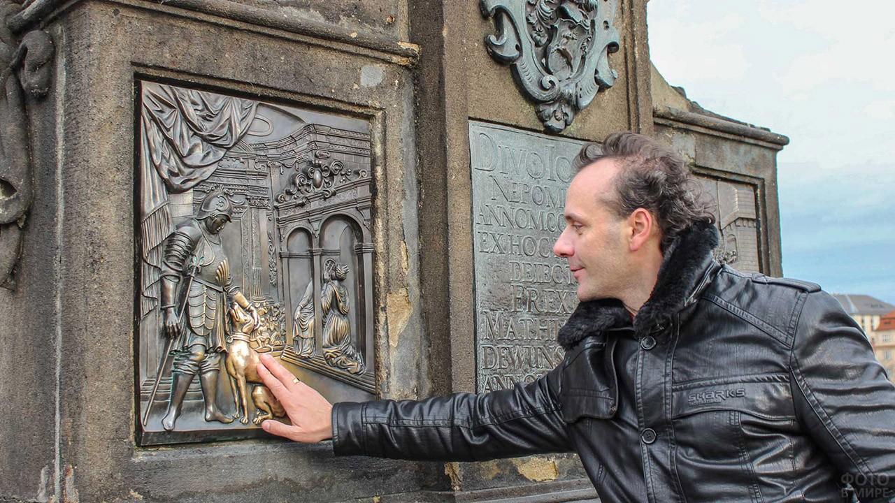 Турист трёт на счастье медную фигурку собачки