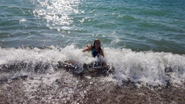 Девочка плещется в набегающих волнах Чёрного моря