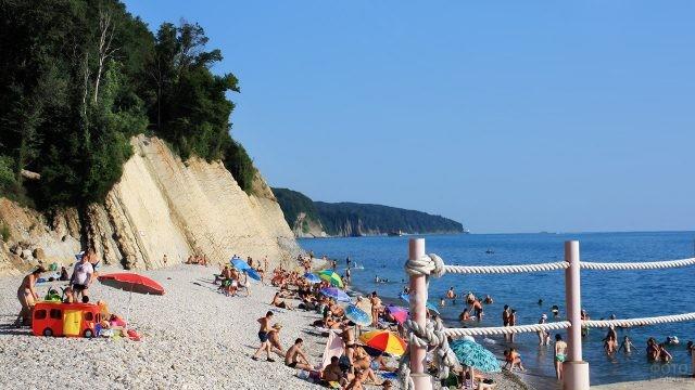 Туристы на пляже у самых перил набережной