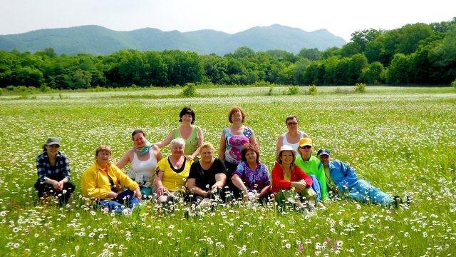 Туристы в весеннем поле с ромашками на горе Шапсуга
