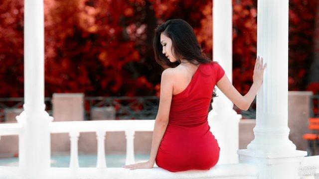 Азиатка в красном платье в белой беседке