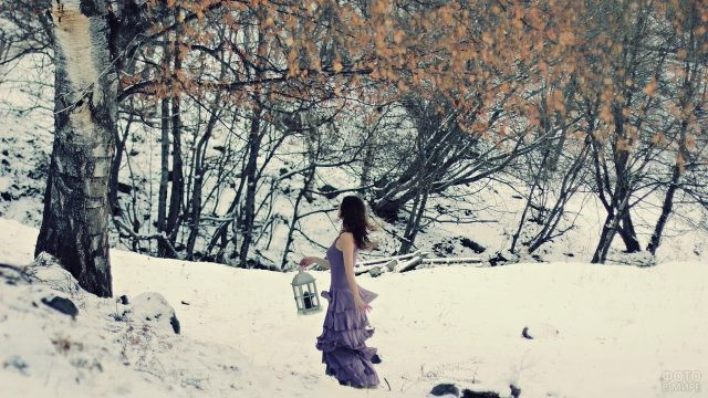 Брюнетка с фонарём в зимнем лесу