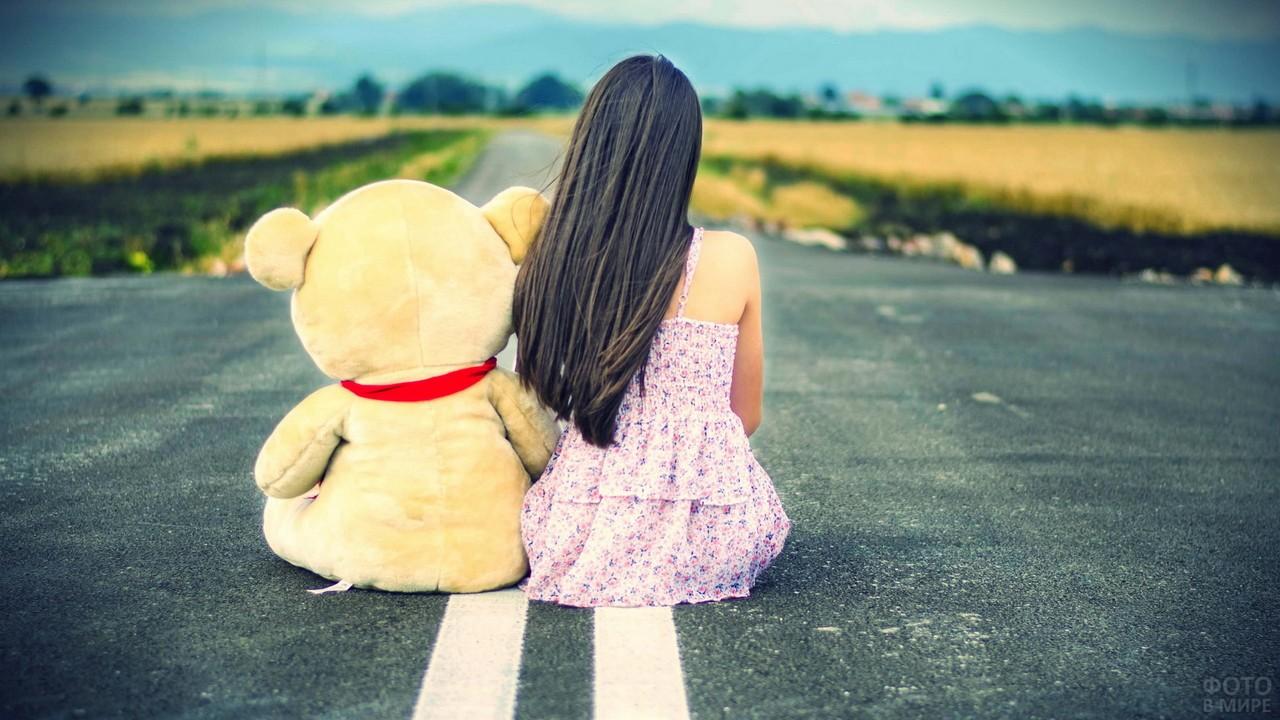 Брюнетка с плюшевым медведем сидят на шоссе