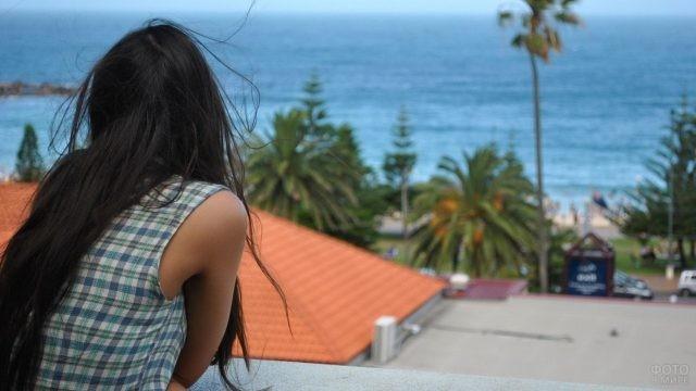 Брюнетка смотрит на море из отеля