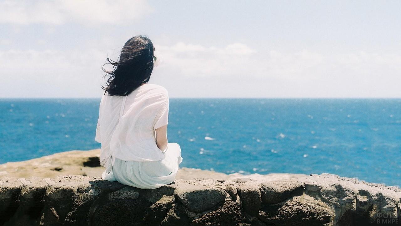 Брюнетка в белой одежде на камнях у моря
