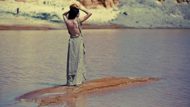 Брюнетка в длинном платье на островке среди моря