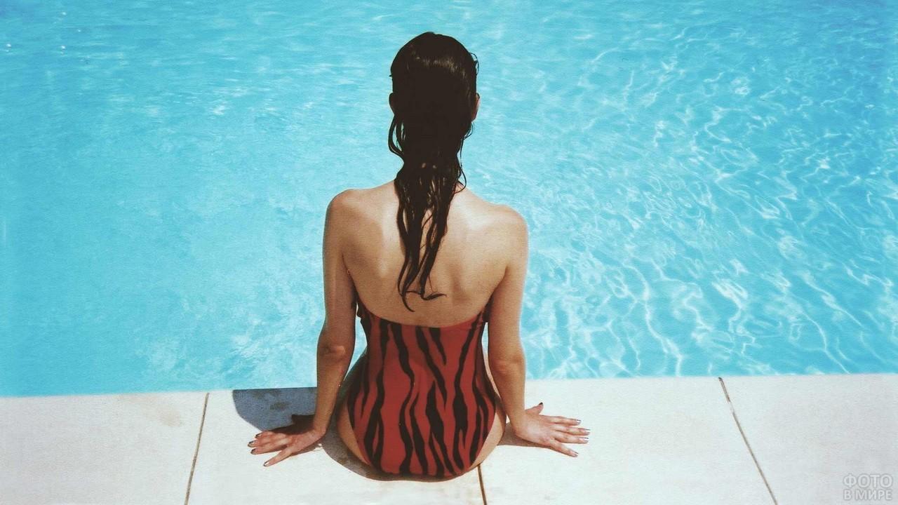 Брюнетка в красно-чёрном купальнике на краю бассейна
