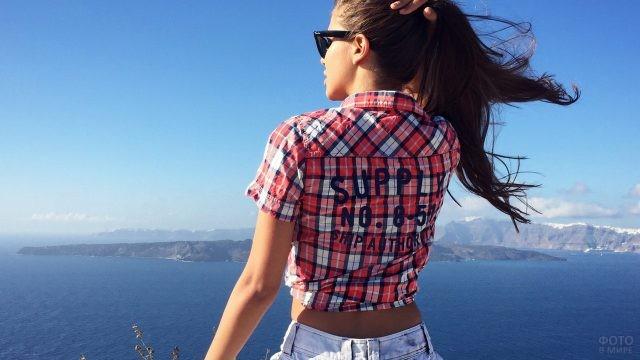 Девушка с хвостом на вершине горы у моря