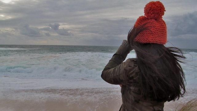 Девушка в красной шапке на берегу волнующегося моря