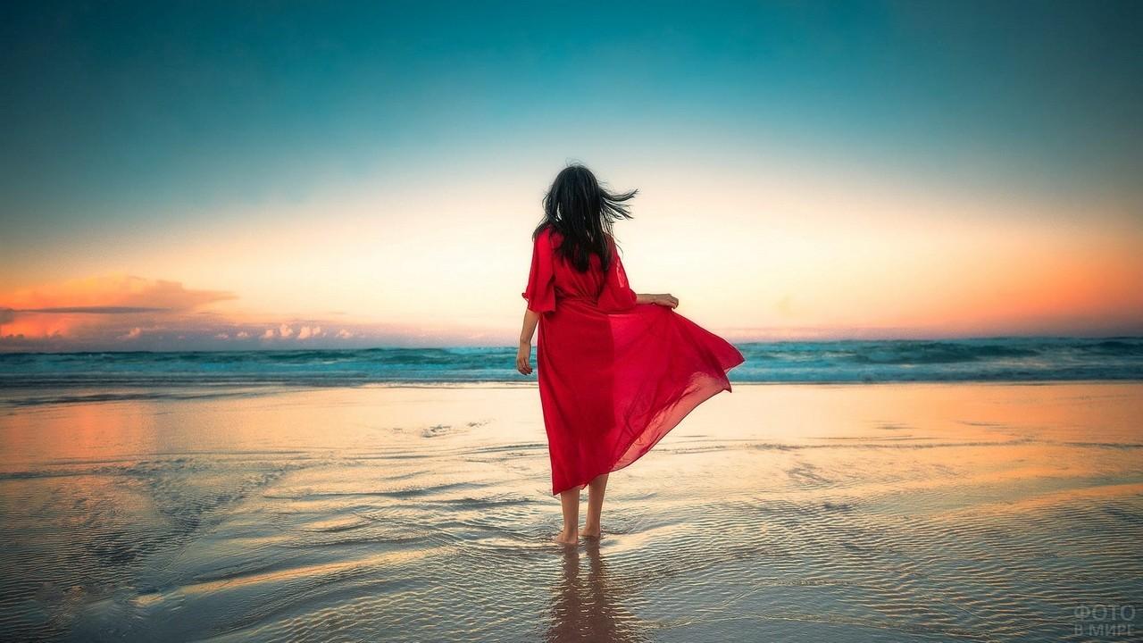Девушка в красном платье стоит в море