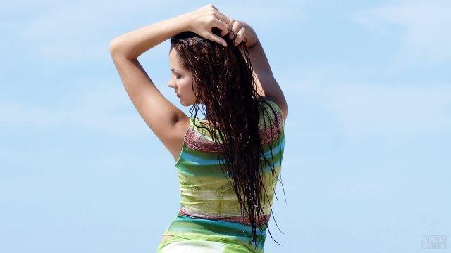Девушка запустила руки в мокрые волосы на фоне неба