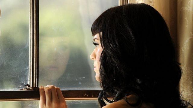 Красивая брюнетка смотрит в окно