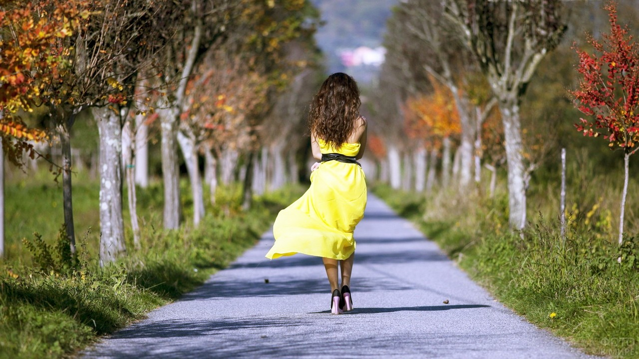 Красотка в жёлтом платье идёт по парку