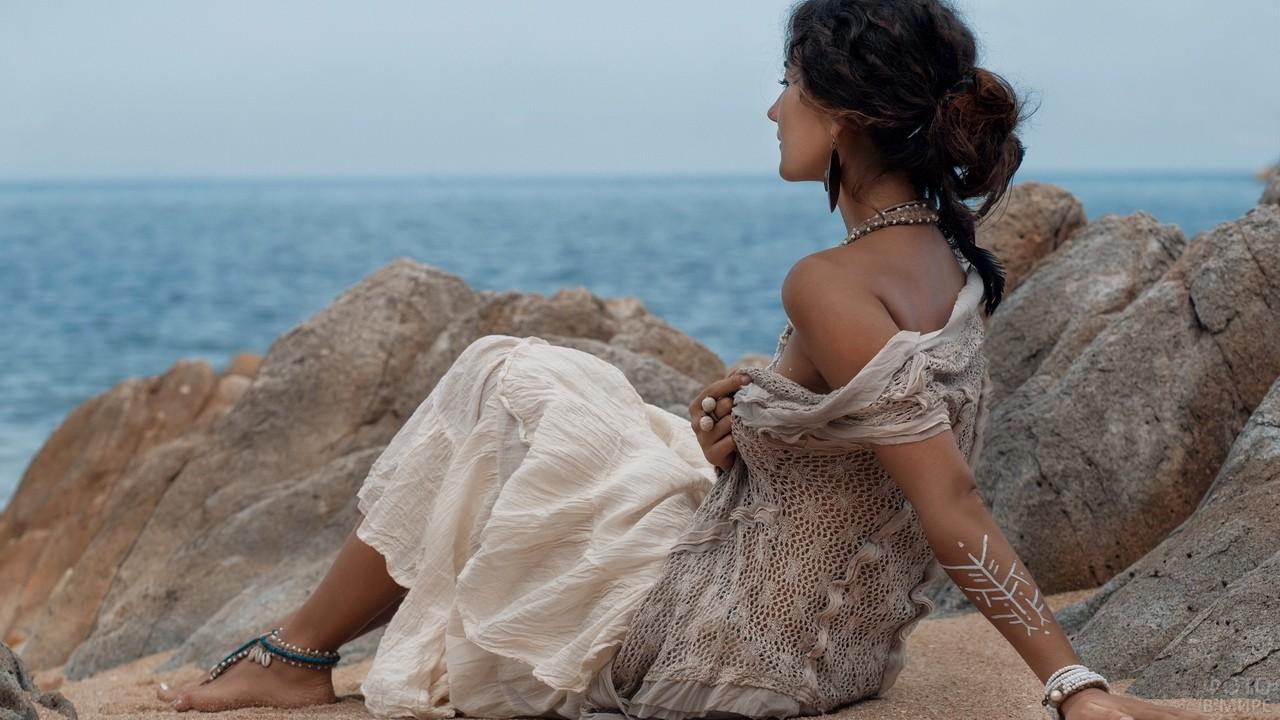 Милая девушка в этническом стиле на камнях