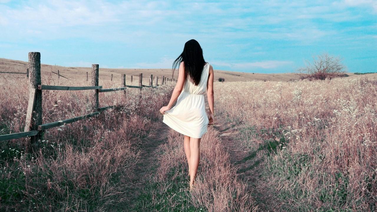 Нежная девушка идёт вдоль забора