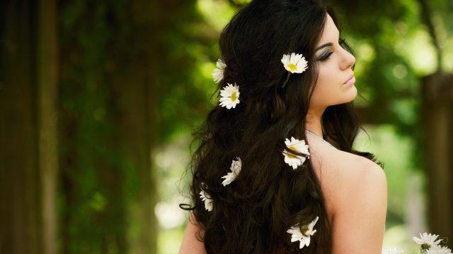 Нежная девушка с ромашками в волосах на природе