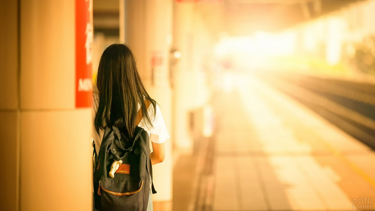 Ожидающая девушка с рюкзаком на перроне