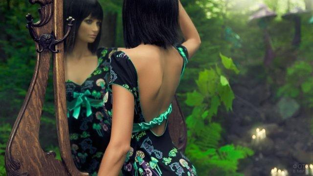 Симпатичная девушка смотрит в зеркало в лесу