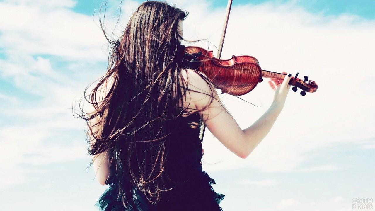Скрипачка с длинными волосами на фоне неба