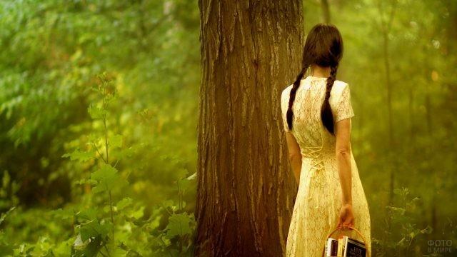 Скромница с косичками и корзиной книг возле старого дерева
