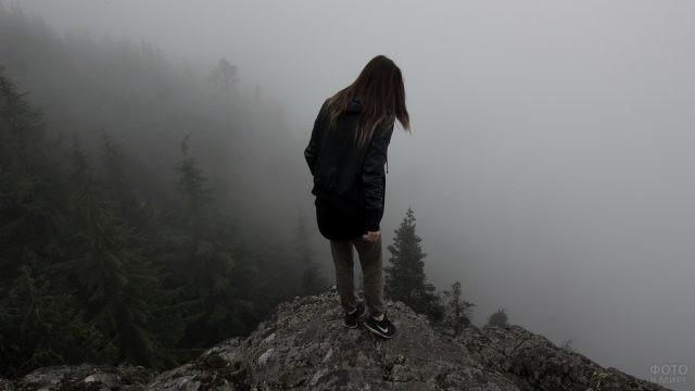 Смелая девушка смотрит в пропасть со скалы