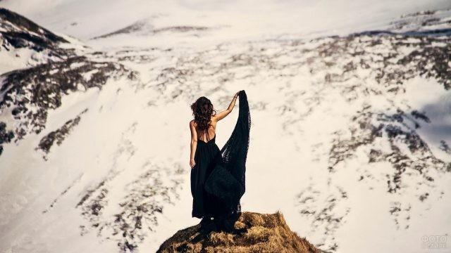 Смелая девушка в чёрном платье стоит на краю скалы