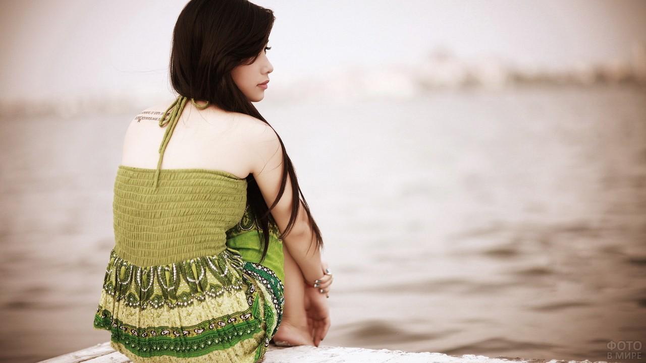 Задумчивая девушка на речном берегу
