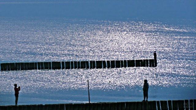 Люди фотографируются на столбиках в море