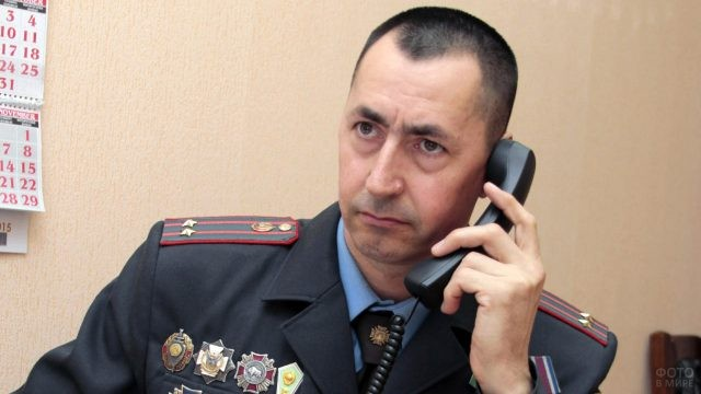 Старший участковый в звании подполковника говорит по телефону