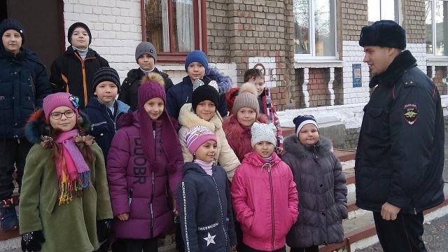 Участковый инспектор полиции на крыльце школы с учениками