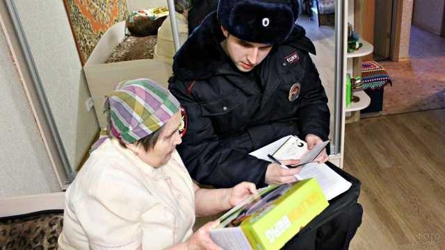 Участковый общается с пенсионеркой в её квартире