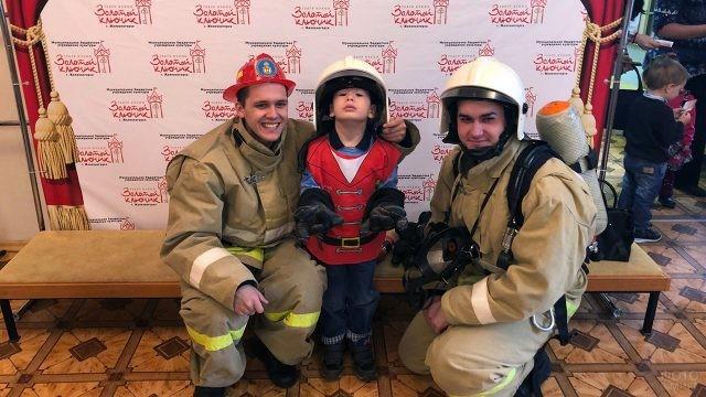 Пожарные фотографируются с мальчиком в каске