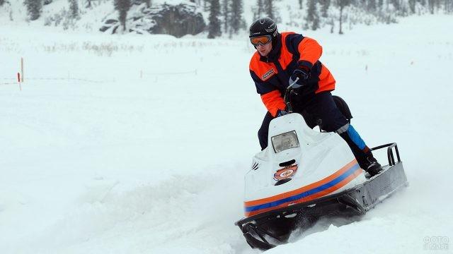 Сотрудник МЧС маневрирует на снегоходе