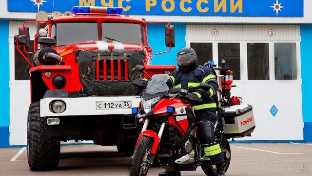 Спасатель МЧС на мотоцикле на фоне пожарной машины