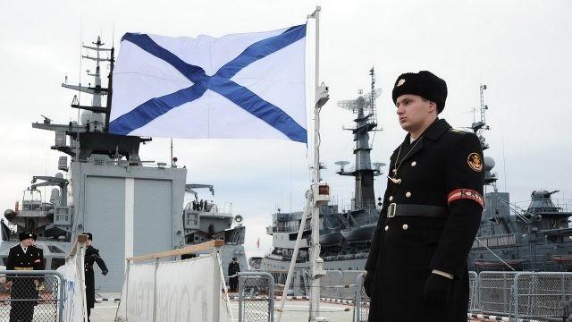 Моряк в шинели возле Андреевского флага