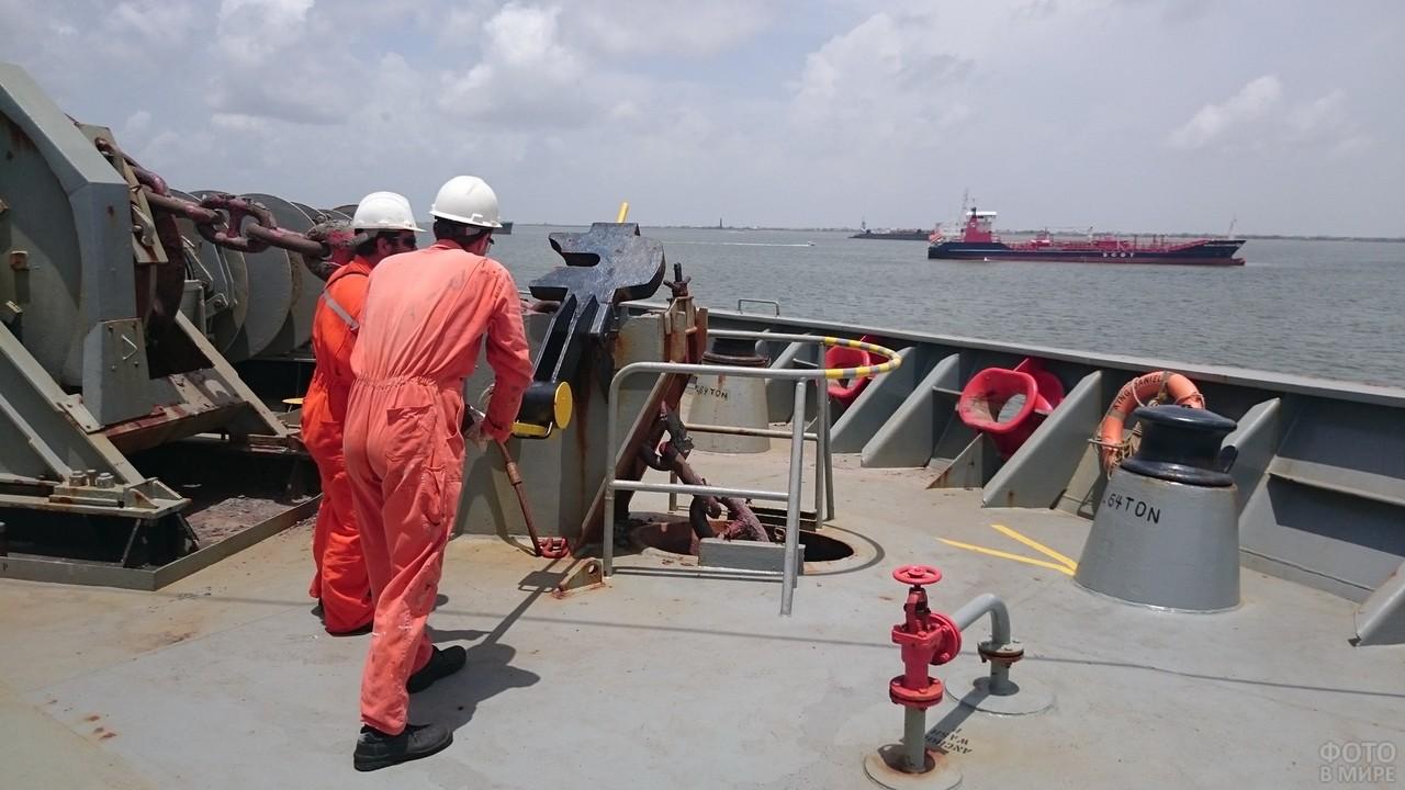 Моряки в оранжевых комбинезонах на танкере