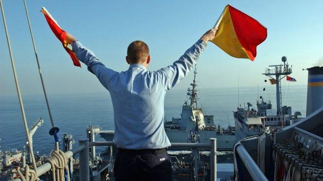 Мужчина сигналит с корабля флажками