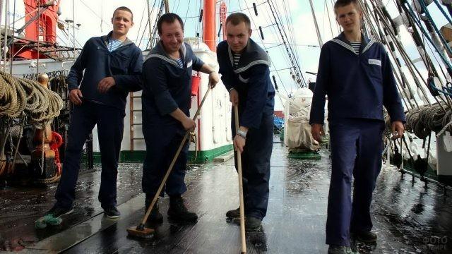 Мужчины драят палубу швабрами