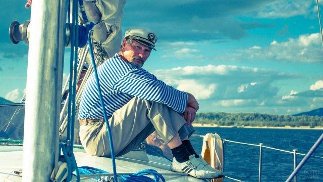 Старый моряк сидит на яхте
