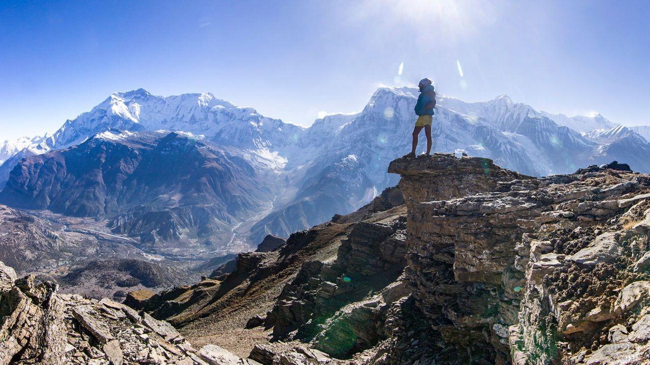 Человек стоит на вершине горы и любуется видом