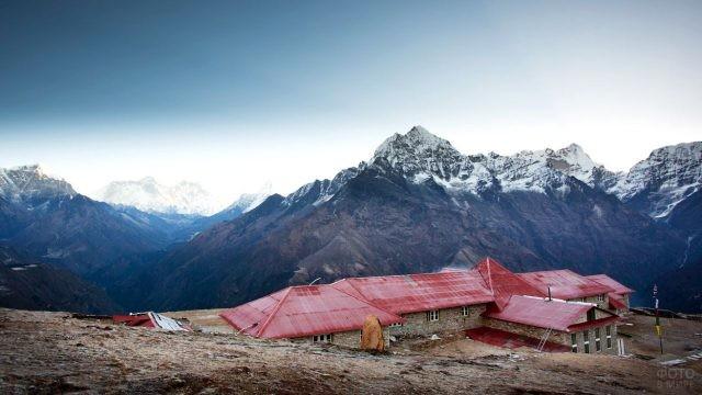 Небольшой дом у обрыва на фоне Гималайских гор