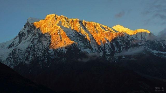 Солнечные лучи освещают вершину горы