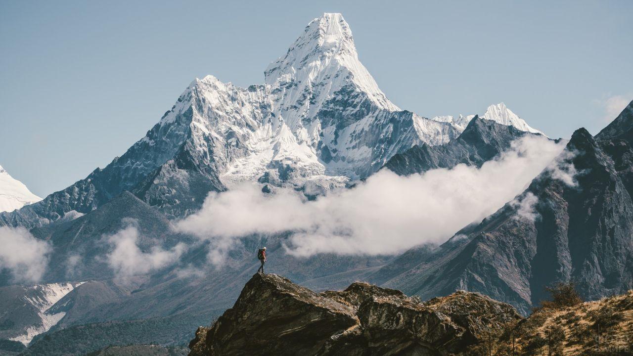 Турист стоит на вершине камня на фоне гор