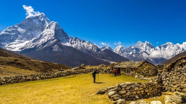 Туристы фотографируются у каменного дома на фоне прекрасных гор