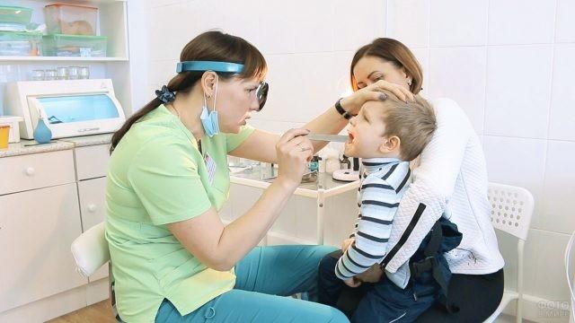 Отоларинголог проводит осмотр ребёнка