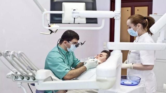 Стоматолог лечит пациента