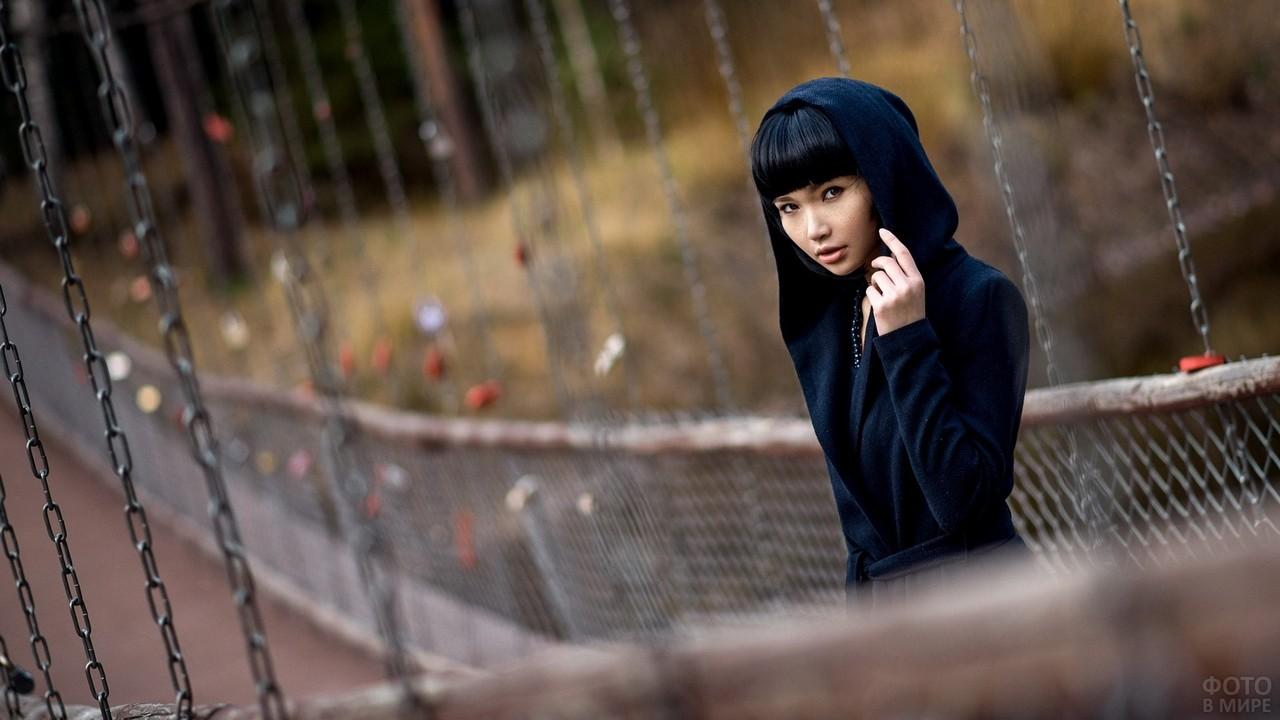 Азиатка в капюшоне на качающемся мосту