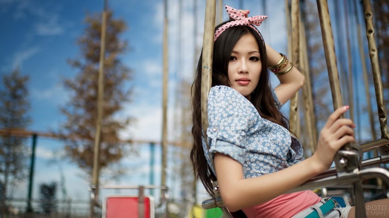 Азиатка в ободке на карусели