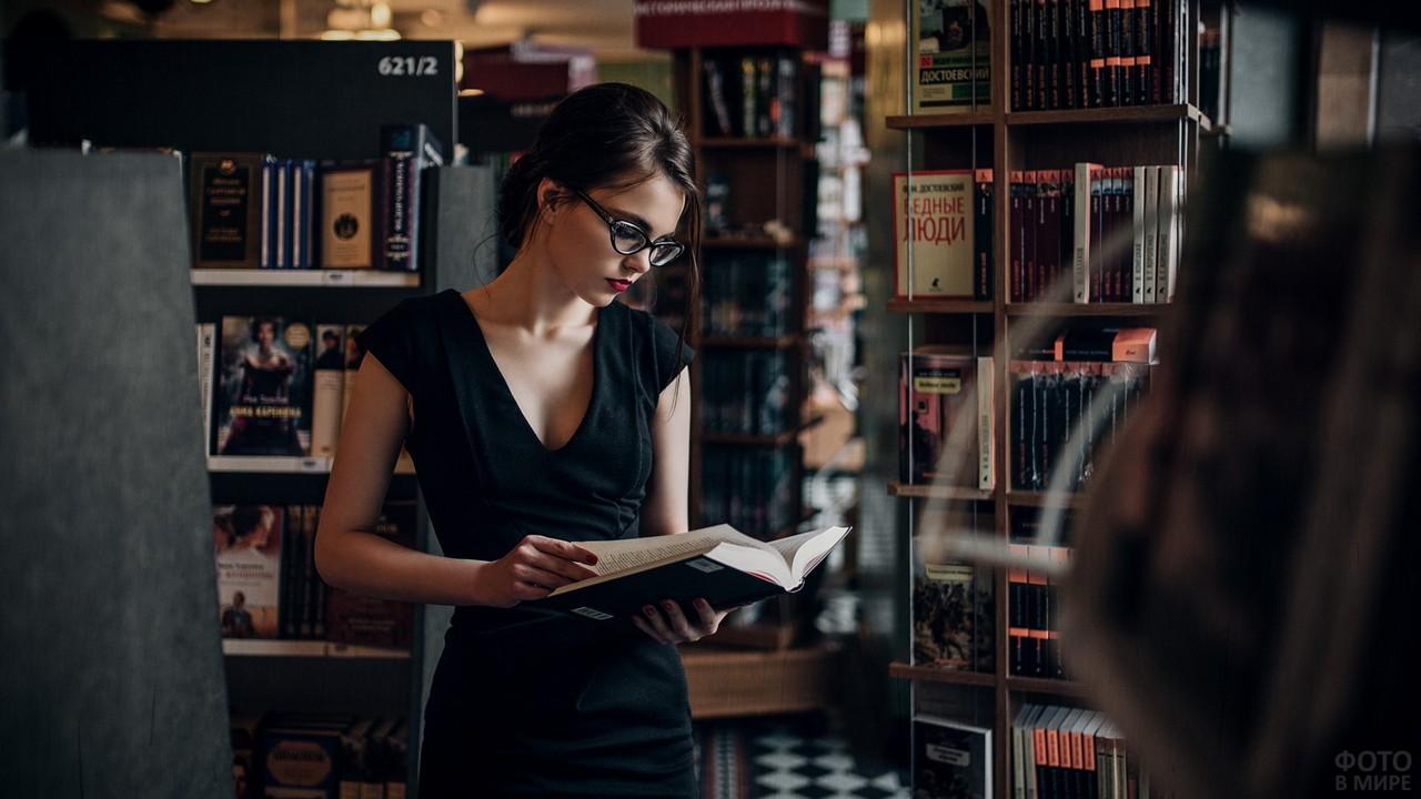 Читательница выбирает книгу в библиотеке